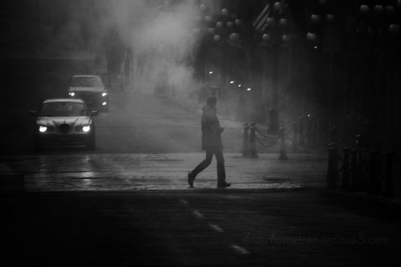 A man crosses a foggy street, car headlight toward