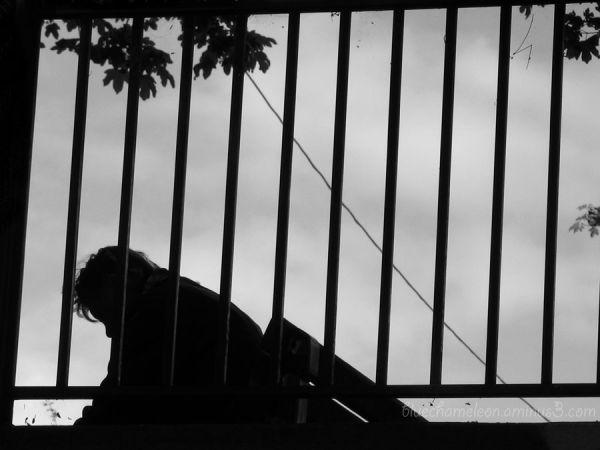 A broken hearted man through a fence