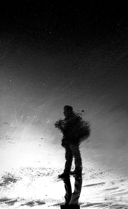 An upside down reflection of a man on a beach