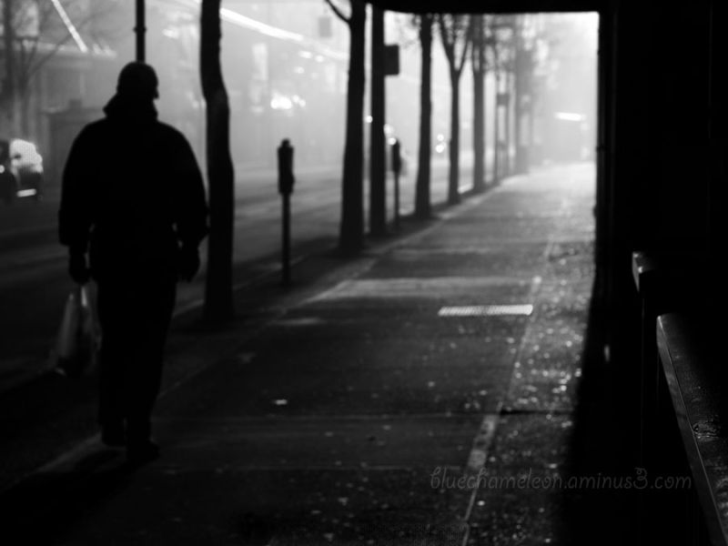 A dark figure walking into a lit street
