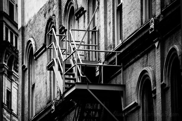 A fire escape and back of a building, gritty.
