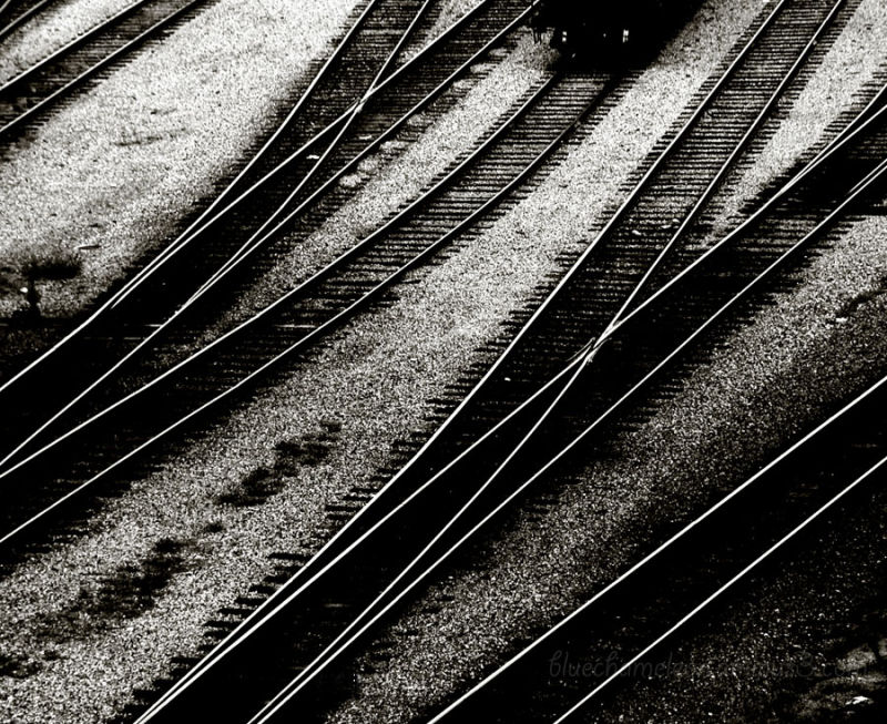 Criss-crossing railway tracks with train coming