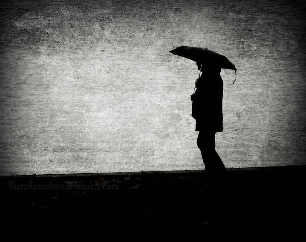 A silhouetted man with an umbrella walking in rain