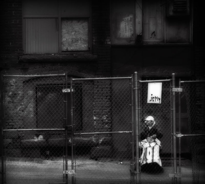 A homeless man in wheelchair in gritty alley