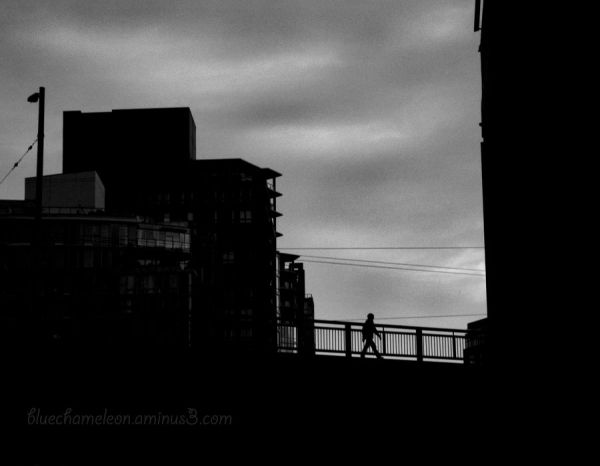 Silhouetted buildings and bridge with man crossing
