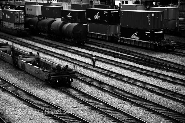A man walking  across  many railroad tracks