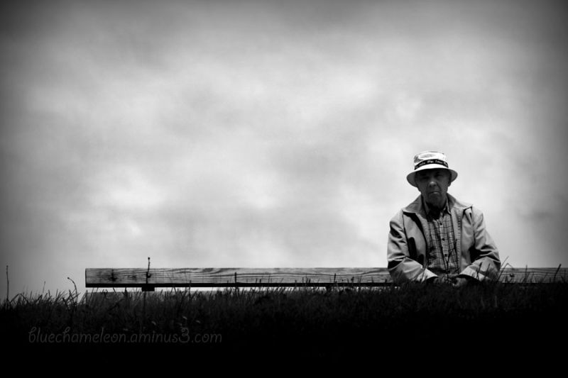 An old man wearing a hat on park bench