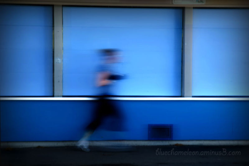 A blurred woman running against a blue wall