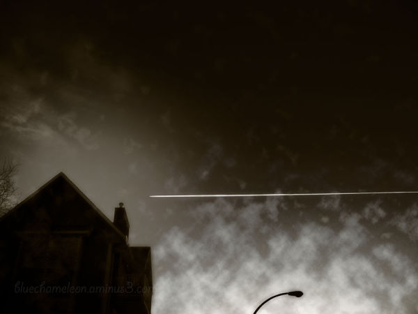 Silhouette of house, lamppost with contrail, cloud