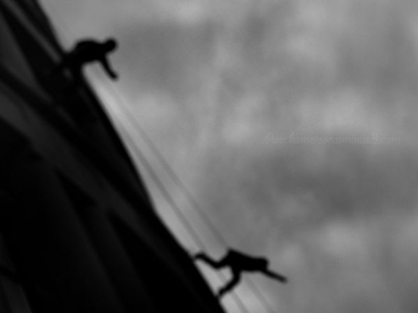 Two silhouetted men on wires hanging from library