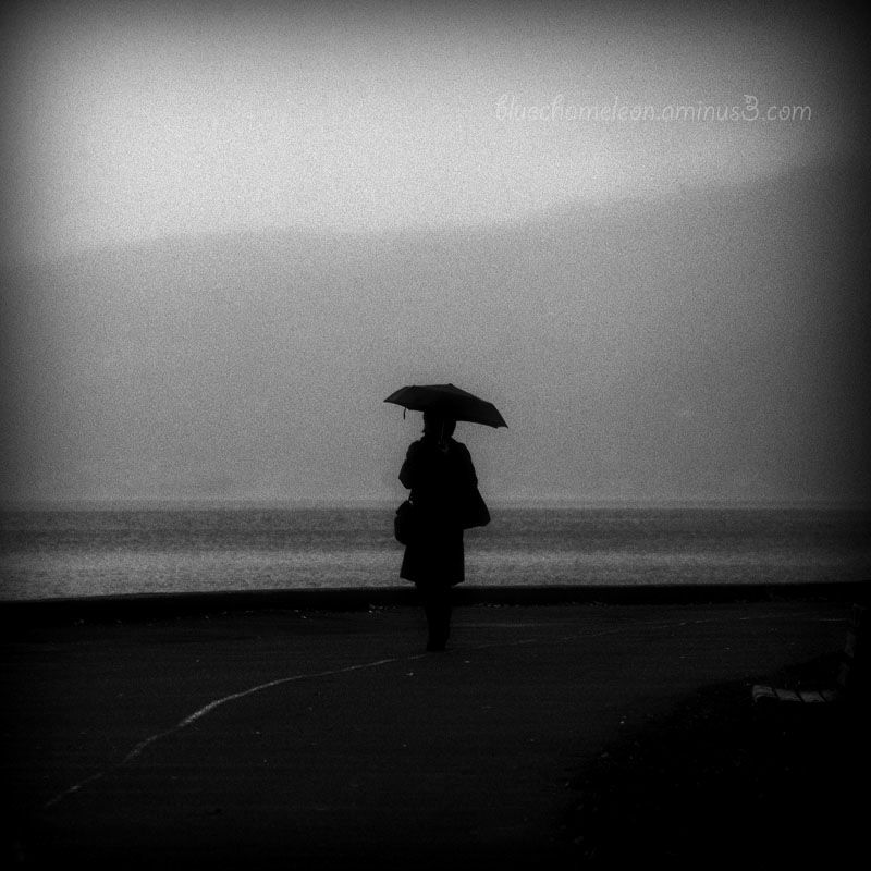 A silhouetted woman with umbrella walking in rain