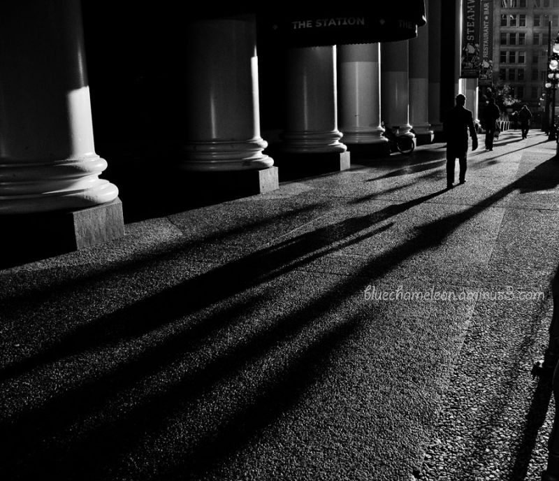 Silhouette men, long shadows, pillars along street