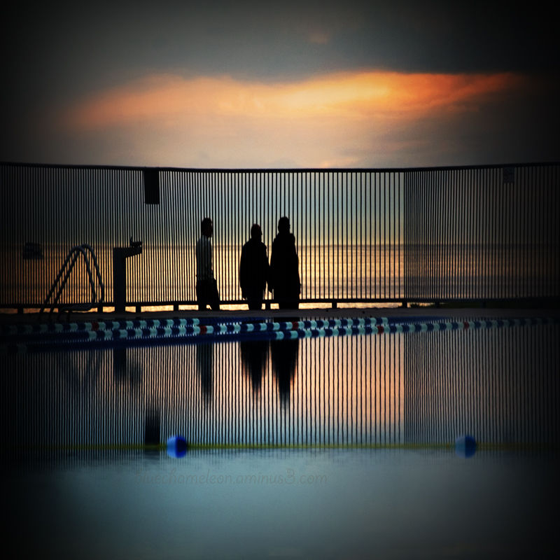 3 silhouetted people in sunset by ocean & pool