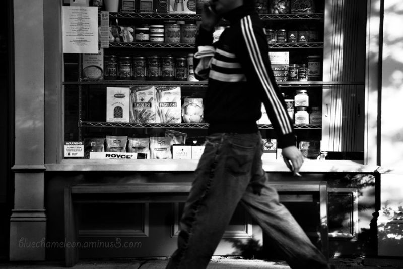 A man holding a cigarette walking by store window