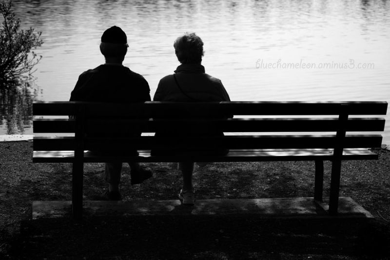 An elderly couple sitting on a bench.