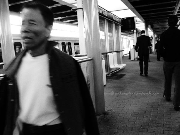 Men in a train station in movement.