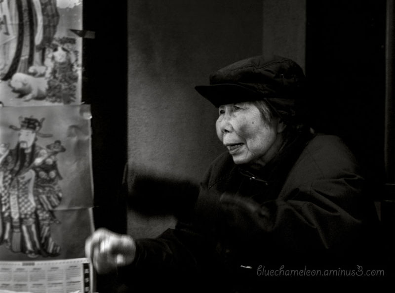 An old Chinese woman selling her papers