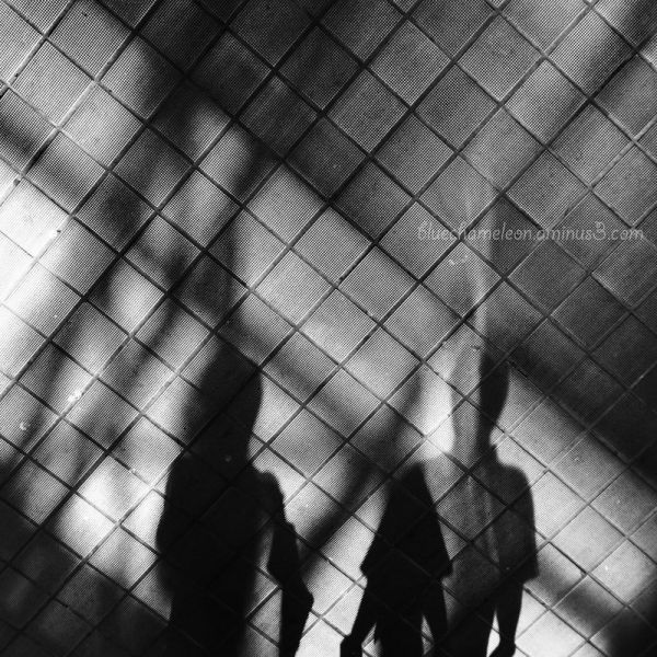 Shadows of people on tiled floor through glass