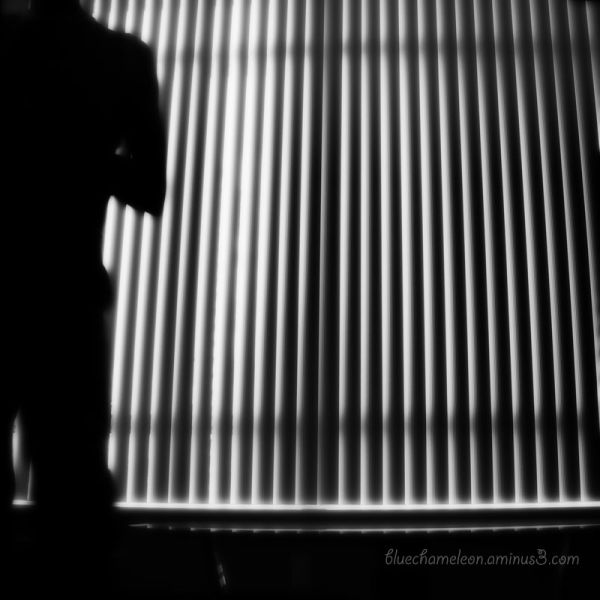 Silhouette of half a man against vertical blinds