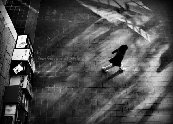A woman running through ghostly shadows