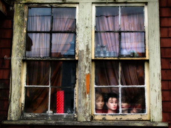 Mannequin heads in window of decaying house