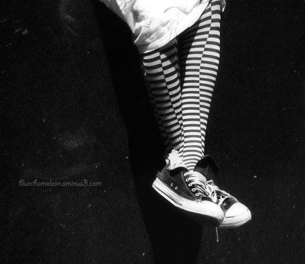 Girls legs with  striped leggings and converse