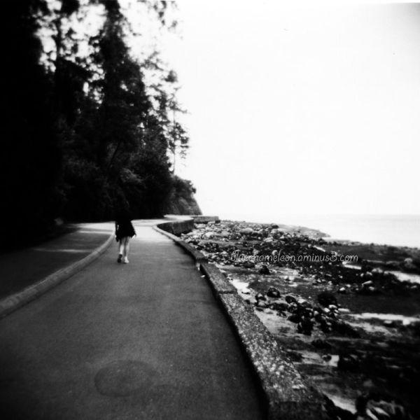 A lone woman walking along curved seawall.