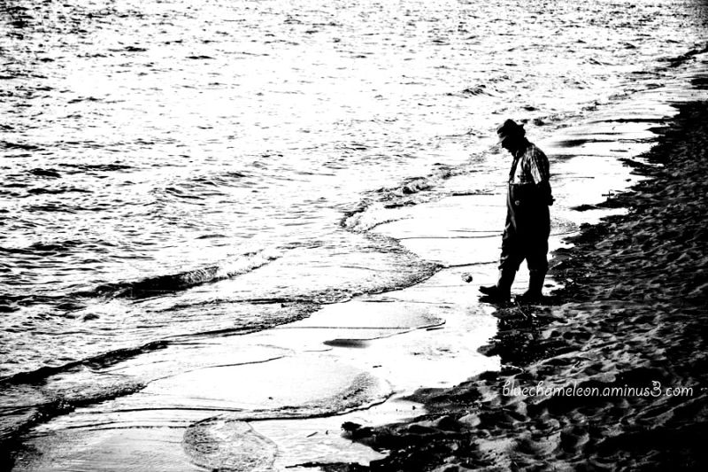 An elderly man wading in ocean at sunset