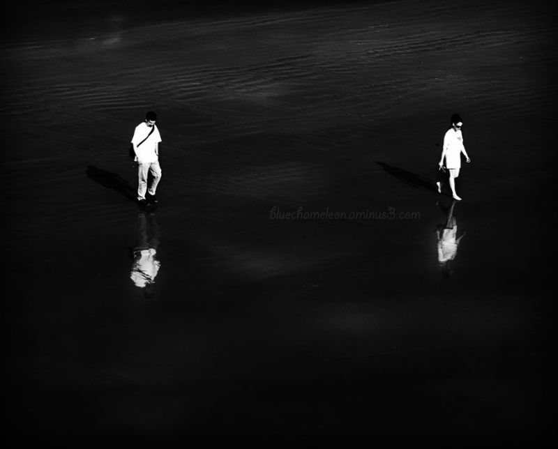 Two people walking on wet beach with reflections