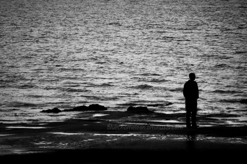 Lone silhouetted man staring into the ocean