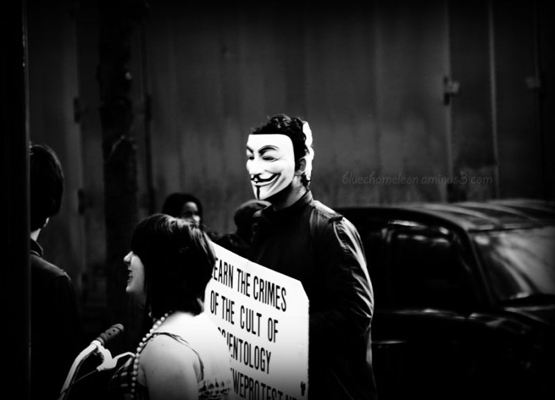 A man wearing 2 masks protesting in streets.