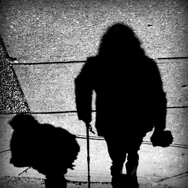 Two shadows looking like hunchbacks on sidewalk