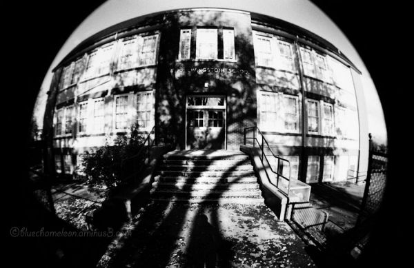A fisheye distortion of an old school with shadows