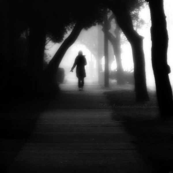 A lone woman walking along sidewalk in fog