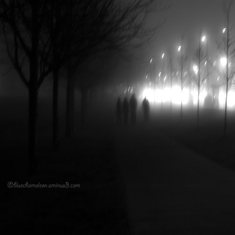 Four blurred figures walking through light & fog