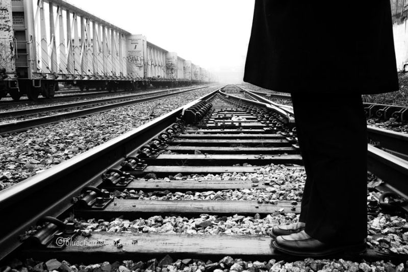 Legs of a man in black on railway tracks
