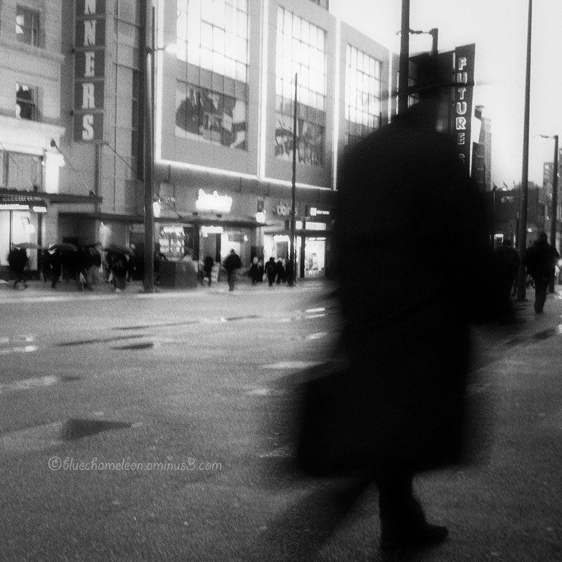 Shadowy blurred man walking down street in rain
