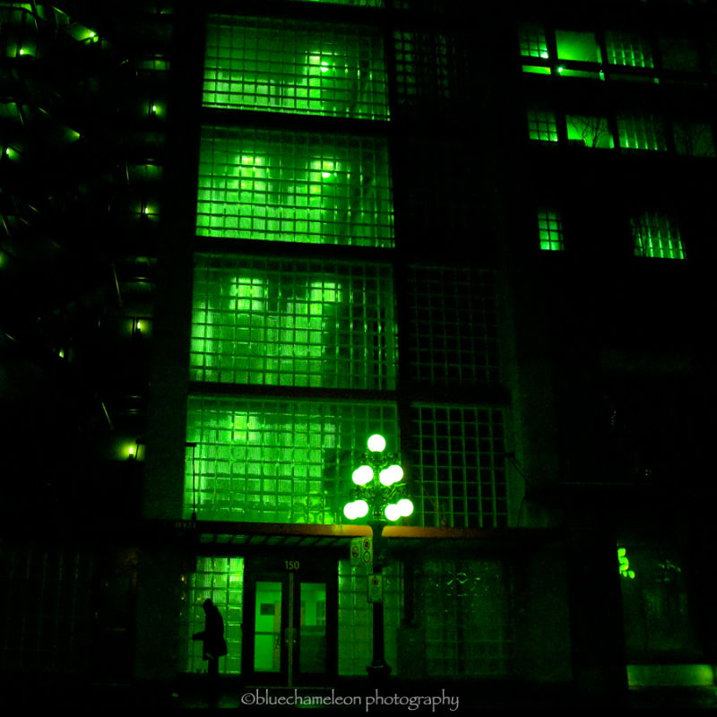 Silhouetted man against green light from building