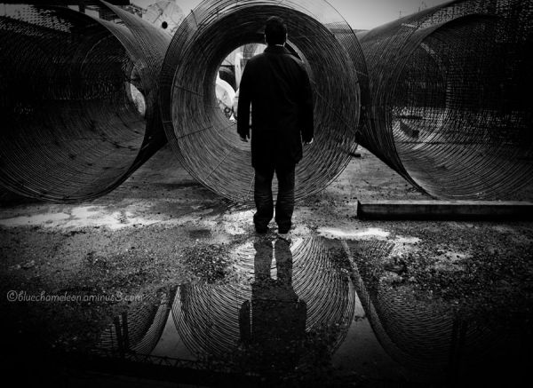 A man standing in front of 3 wire cylinders