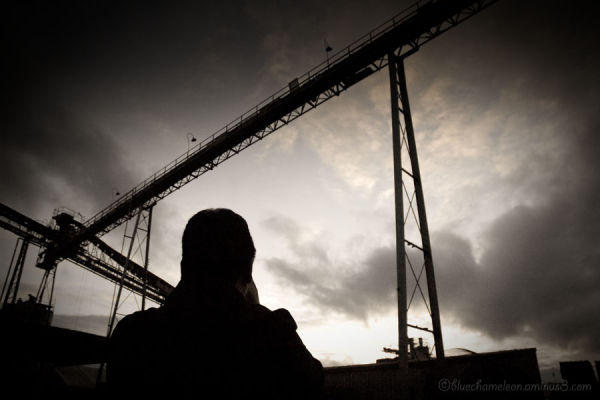 A man standing below cranes and dramatic sky