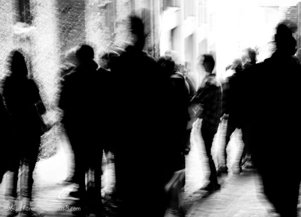 A crowd of blurred people in an alley