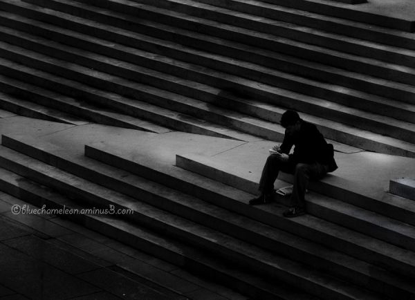 A lone man sitting in a maze of stairs, reading.