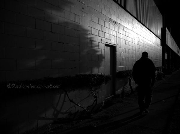 Silhouetted man walking against strang fence, wall