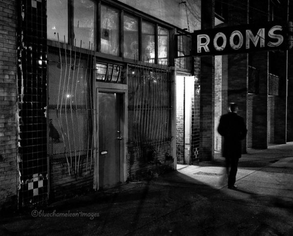 "A man walking by a sign that says ""Rooms"" in city"
