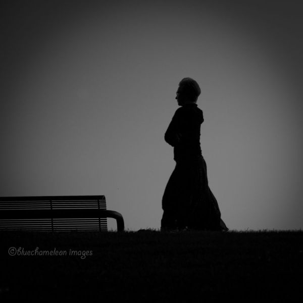 A silhouetted woman moving through twilight