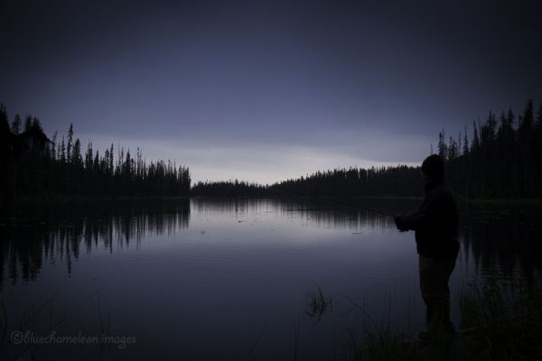 A man fishing at dusk with reflections in lake