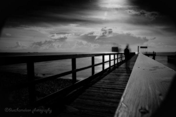 2 silhouettes in motion, dreamlike on long pier