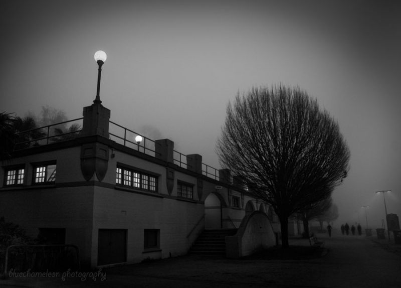 Silhouetted people wasking past structure in fog