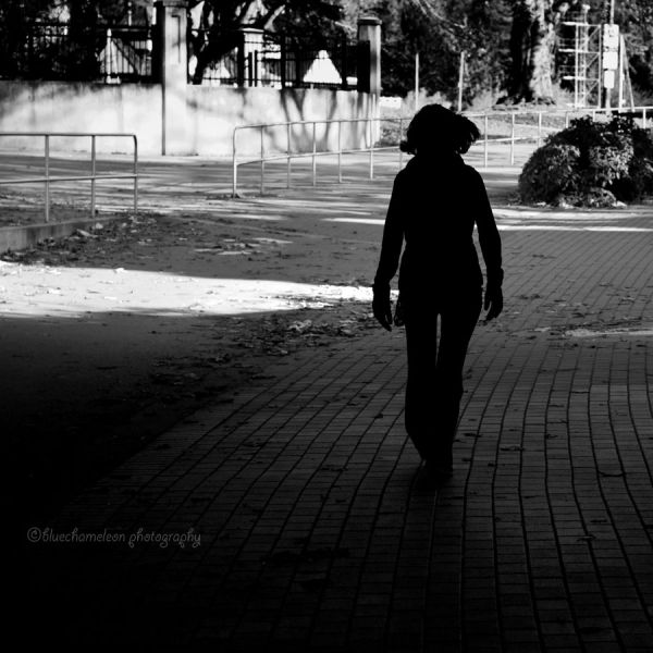 Silhouetted woman walking along park path