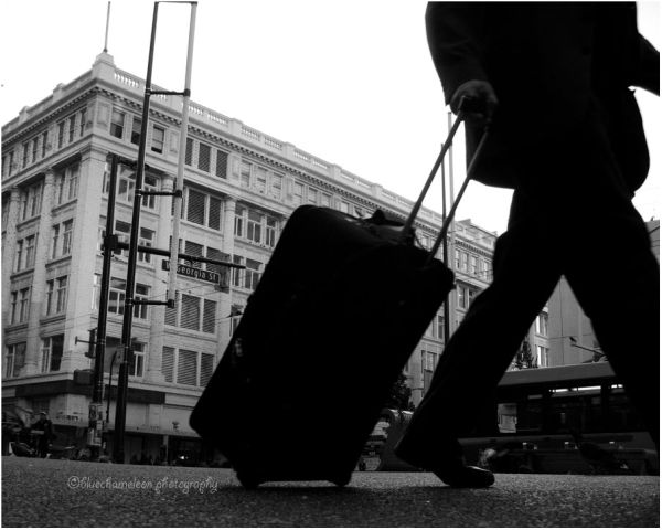 Silhouetted man on street pulling suitcase